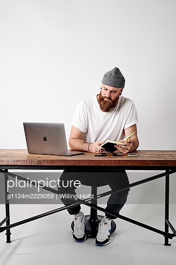 Mann am Schreibtisch mit Laptop und Terminplaner - p1124m2229059 von Willing-Holtz