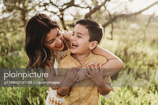 Close up view of mother and son hugging and laughing together - p1166m2131150 by Cavan Images
