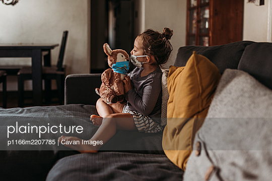 Side view of preschool age girl with mask on cuddling masked doll - p1166m2207785 by Cavan Images