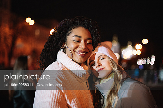 Portrait of happy girlfriends standing in city at night - p1166m2258311 by Cavan Images