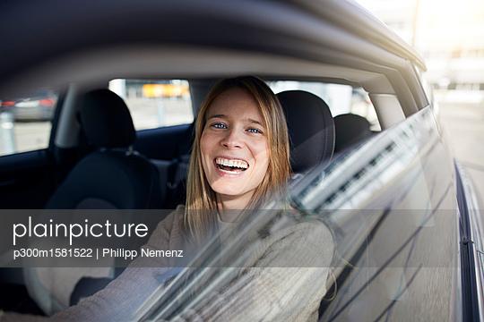 Portrait of laughing young woman sitting in car - p300m1581522 von Philipp Nemenz