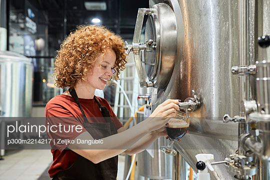 Woman working in craft brewery tapping beer from tank - p300m2214217 by Zeljko Dangubic