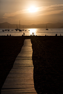 People on an Italian beach silhouetted by the setting sun and reflections on the sea surface - p1057m1591713 by Stephen Shepherd