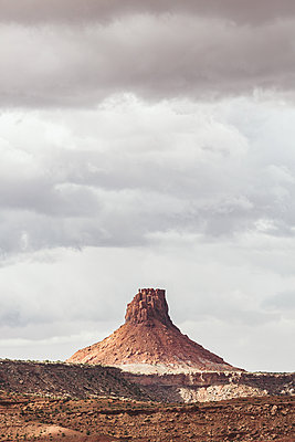 elaterite butte seen from the south under rain clouds in the maze utah - p1166m2174285 by Cavan Images