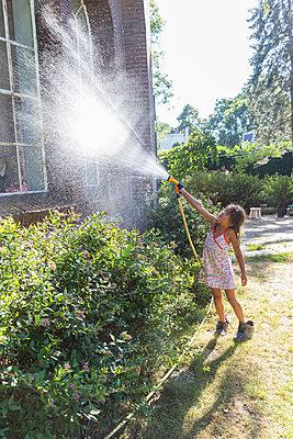 Kleines Mädchen bespritzt Fenster mit einem Gartenschlauch - p1231m2013525 von Iris Loonen