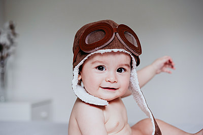 Cute baby boy wearing aviator cap while sitting at home - p300m2225226 by Eva Blanco