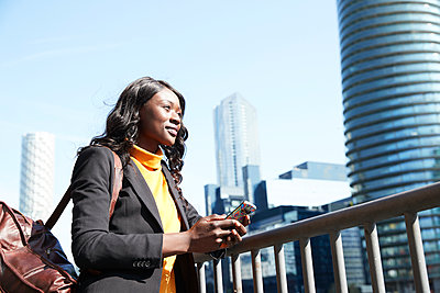 Smiling businesswoman looking away while standing by railing on sunny day - p300m2241040 by Pete Muller