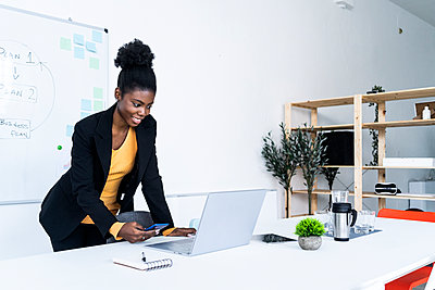 Smiling young Afro businesswoman using smart phone while looking at laptop in office - p300m2251955 by Giorgio Fochesato