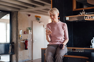 Smiling businesswoman with coffee cup using mobile phone while sitting on kitchen counter at home - p300m2267813 by Robijn Page
