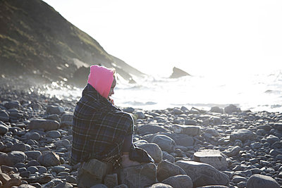 Girl in deep thought on rocks by sea - p429m2098385 by Janeycakes Photos