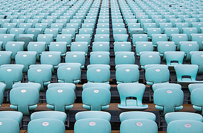 Rows of blue seats at empty open air stadium - p429m2098591 by Henn Photography