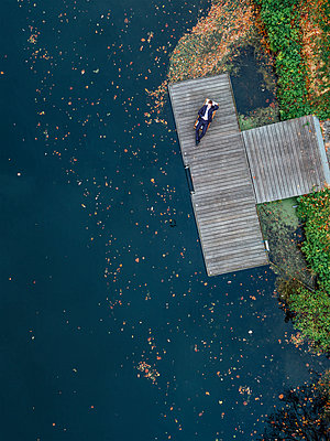 Business man resting on boardwalk on the waterfront, aerial view - p586m1088294 by Kniel Synnatzschke