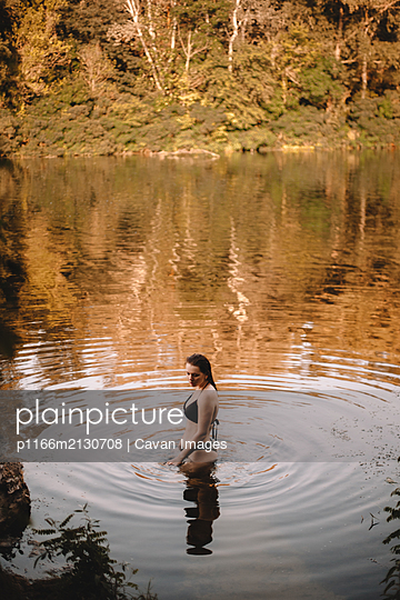 Sensual woman standing in lake in forest - p1166m2130708 by Cavan Images
