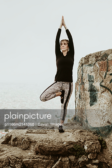Young woman practicing yoga, asana with raised hands watching - p1166m2141068 by Cavan Images