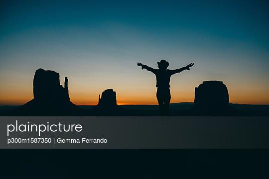USA, Utah, Woman enjoying sunrise in Monument Valley - p300m1587350 von Gemma Ferrando