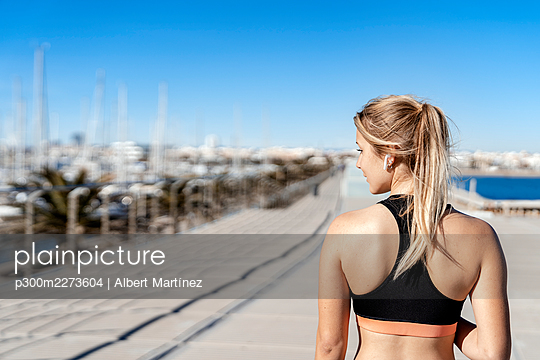 Female athlete with in-ear headphones looking away while standing on boardwalk during sunny day - p300m2273604 by Albert Martínez