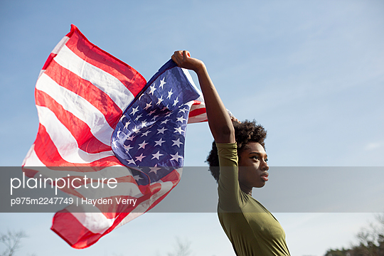 Dunkelhäutige Frau schwenkt die amerikanische Flagge - p975m2247749 von Hayden Verry