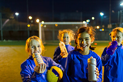 Portrait smiling girls soccer team taking a break from practice, drinking water on field at night - p1023m2035240 by Paul Bradbury
