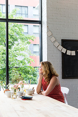 Thoughtful woman with hand on chin looking through window while sitting in cafe - p1166m1489922 by Cavan Images
