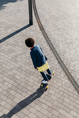 Young businessman riding skateboard on a square - p300m2058902 by Josep Rovirosa
