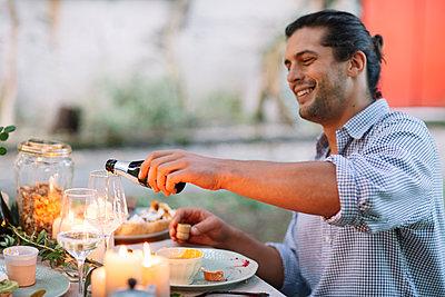 Man pouring out sparkling wine at garden table - p300m2068387 von Alberto Bogo