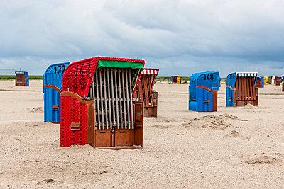 Germany, Nessmersiel, hooded beach chairs on sandy beach - p300m2102705 by Ega Birk