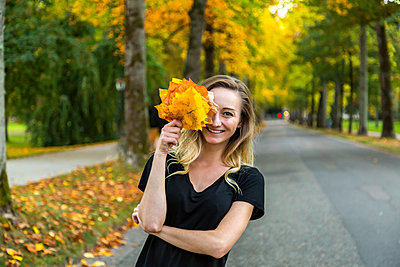 Portrait of laughing woman with bunch of autumn leaves on avenue - p300m2275825 by JLPfeifer