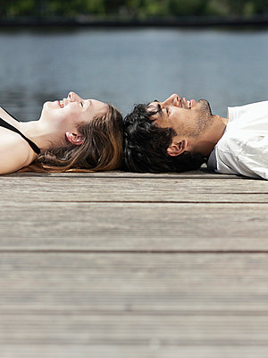 A young couple lying on a jetty head to head - p3017791f by Paul Hudson