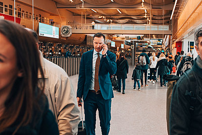 Mature businessman using mobile phone while walking with crowd in airport - p426m1580043 by Maskot