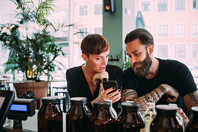 Bearded young man with brown hair and tattoos and young woman with short hair sitting in a bar, looking at mobile phone.  - p429m2200830 by Eugenio Marongiu
