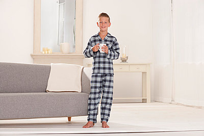 Boy in pajamas with mug in living room - p429m696596 by Patrick Wittmann