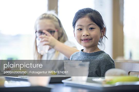 Portrait of smiling schoolgirl with classmate in school canteen - p300m2005293 von Fotoagentur WESTEND61