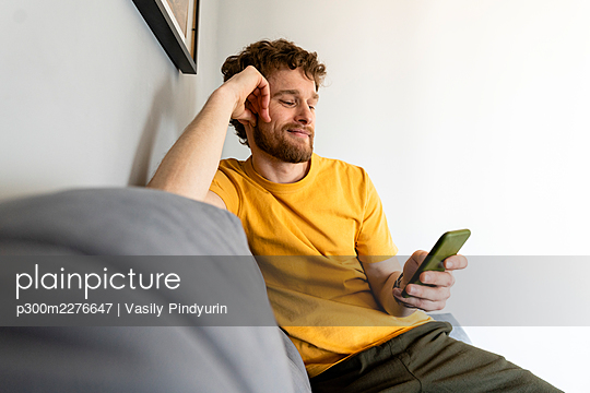 Smiling man using mobile phone while sitting on sofa at home - p300m2276647 by Vasily Pindyurin
