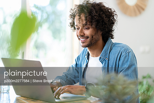 Smiling businessman working on laptop at home - p300m2277584 by Steve Brookland