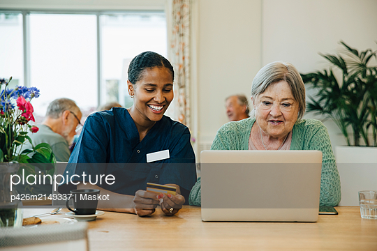Smiling female caregiver assisting senior woman doing online shopping with credit card and laptop in nursing home - p426m2149337 by Maskot