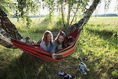 Sisters and brother taking selfie in rural summer hammock - p1192m1490371 by Hero Images