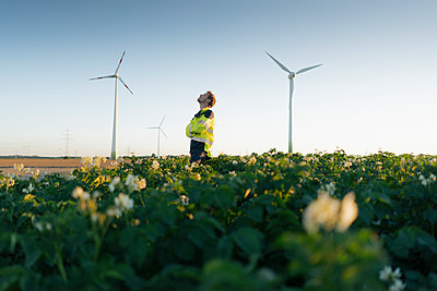 Engineer standing in a field at a wind farm - p300m2058921 von Gustafsson