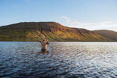 Man fishing in lake - p312m2051424 by Hans Berggren