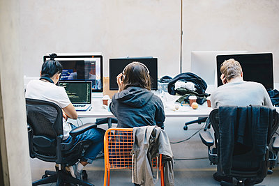 Rear view of programmers using computers at desk in office - p426m1493983 by Maskot