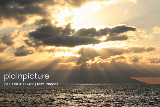 Sunset over the ocean, shafts of sunlight falling to the water, and layers of clouds.  - p1100m1017743f by Mint Images