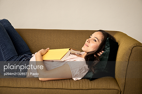 Woman with book lying on sofa - p294m2132897 by Paolo