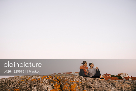 Male friends sitting on rock against clear sky - p426m2296131 by Maskot