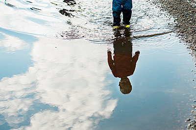 Low section of baby boy standing on wet street during monsoon - p1166m1543970 by Cavan Images