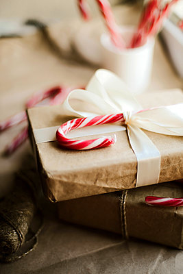 Christmas present with candy canes on wooden table - p1166m2106059 by Cavan Images