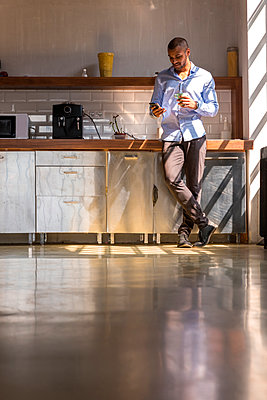 Young entrepreneur standing in company kitchen, drinking coffee, using smartphone - p300m1537506 by Spectral