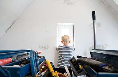 Boy looking out of window in attic to be renovated with toolbox in foreground - p300m2083649 by Michelle Fraikin