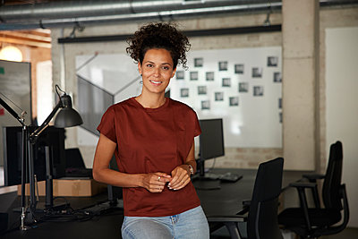 Smiling businesswoman at workplace - p300m2294147 by Rainer Berg