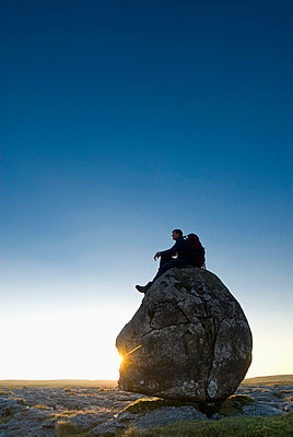 Man Sitting On Head-Shaped Boulder At Dusk, Twisleton Scars, Near Ingleton, Yorkshire Dales National Park, North Yorkshire, England. - p442m839931 by Ian Cumming