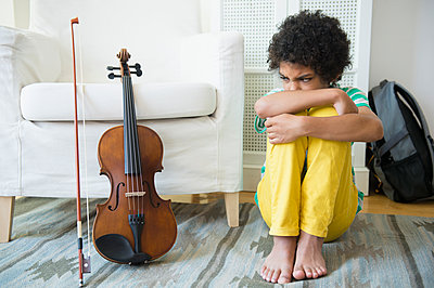 Angry mixed race boy refusing to practice violin - p555m1421091 by JGI/Jamie Grill