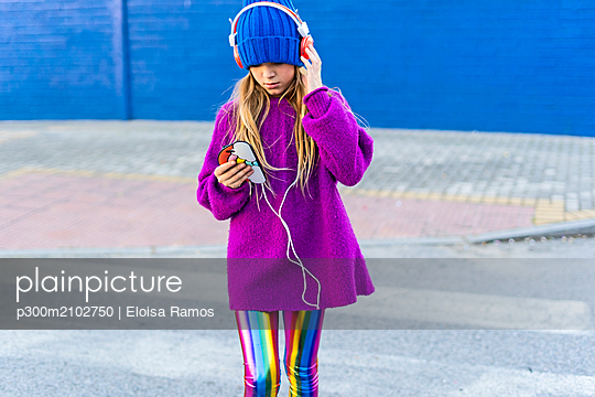 Girl wearing blue cap and oversized pink pullover listening music with headphones and smartphone - p300m2102750 by Eloisa Ramos